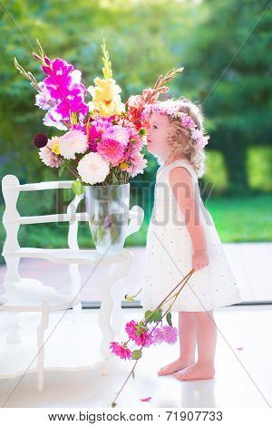 Little Girl Smelling Flowers At Home