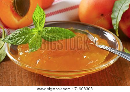 detail of ripe apricots and bowl of apricot jam on wooden table