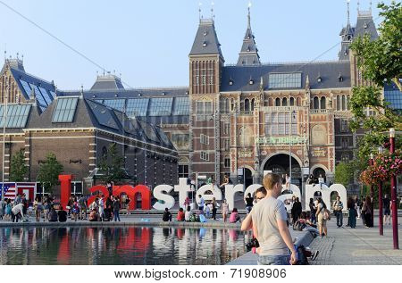 AMSTERDAM - JULY 26: The Rijksmuseum area with with the walking people on 26 July 2014 in Amsterdam, Netherlands. From the front, visible big letters I AMSTERDAM.