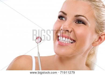 woman is smiling while being at the dentist