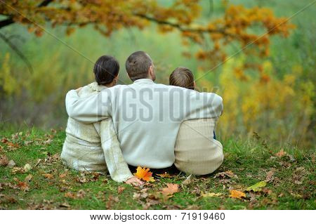 Family sitting in autumn park