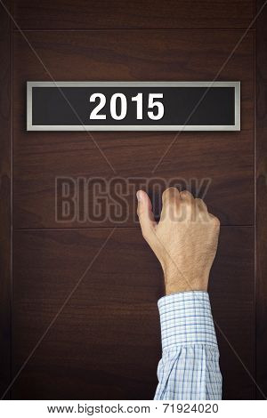 Businessman Knocking On Door With Number 2015