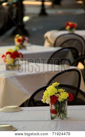 Outdoor restaurant tables with vases of flowers