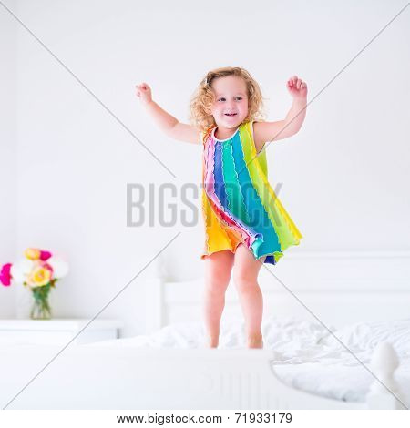 Cute little curly toddler girl jumping on a big white bed