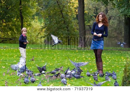 Mother And Son Feeding Pigeons In A Park