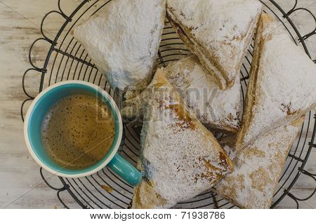 Flakey pastries on rack with coffee