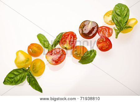 Sliced cherry tomatoes and basil leaves on white background