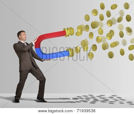 Businessman in suit holding big magnet and attracts money