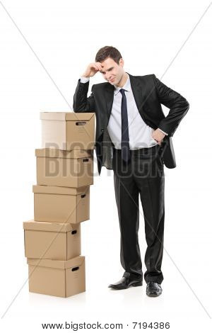 Thoughtful businessman with paper boxes