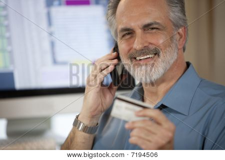 Businessman Paying Over Phone With Credit Card