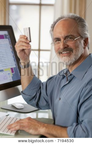 Businessman Sitting At Computer With Credit Card