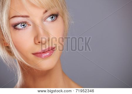 Close up portrait of beautiful young woman face. Isolated on gr