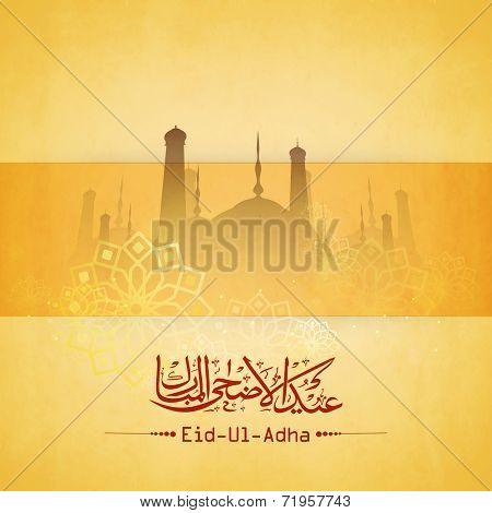 Arabic islamic calligraphy of the text Eid-Ul-Adha with mosque on floral design decorated yellow background.