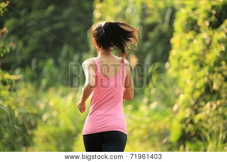 Woman runner running at forest trail