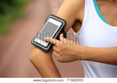Runner athlete listening to music from smart phone mp3 player smart phone armband.woman fitness jogg