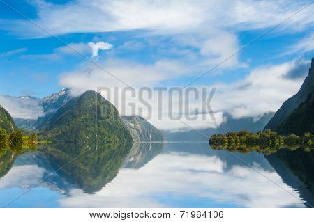 Famous Mitre Peak rising from the Milford Sound fiord and reflecting in water. Fiordland national park, New Zealand