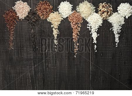 Border Frame made of colorful blend several varieties grain rice heap in a rustic wooden surface background
