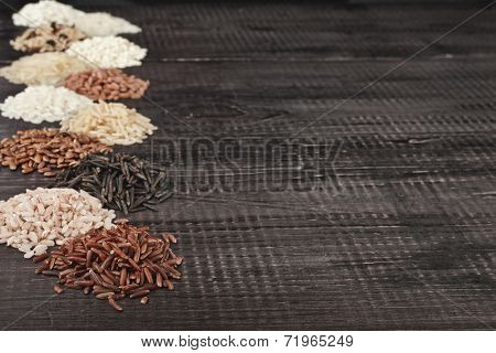 Frame made of several varieties whole grain rice heap in a rustic wooden surface background