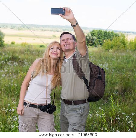 Happy couple taking selfie photo with smart phone hiking in the valley.