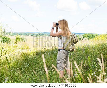 Hiker looking in binoculars enjoying spectacular view on the valley. Young woman using binoculars in