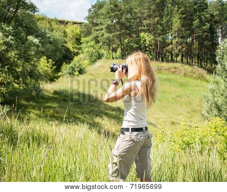 Young woman photographer in the forest. Nature photographer taking pictures outdoors during hiking t