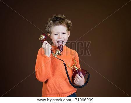 Child yelling on a retro phone. An angry boy screaming in telephone receiver on brown background.