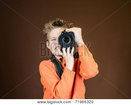 Child in studio with professional camera. Boy using a camera on brown background.