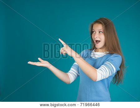 Beautiful woman pointing showing blank area for sign or copy spase on blue background.