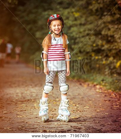 happy little girl on roller skates in the autumn forest