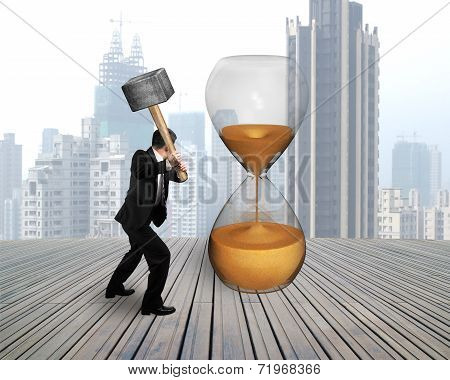 Businessman Holding Hammer To Hit Hour Glass