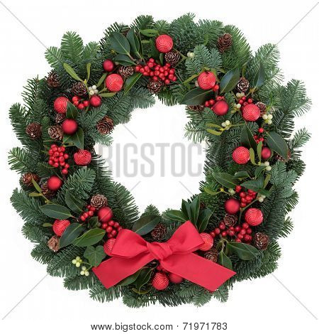 Christmas wreath with red bauble decorations and bow, holly, ivy, mistletoe, fir and pine cones over white background.