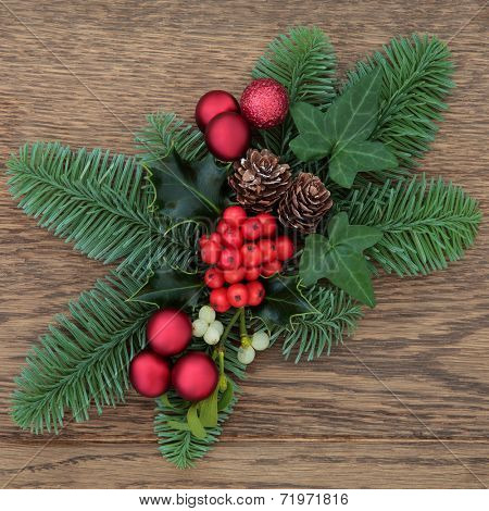 Christmas floral decoration with red baubles, fir, holly, ivy mistletoe and pine cones over oak wood background.