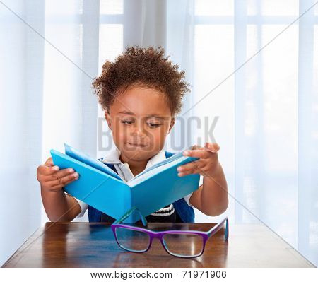 Little schoolboy read book in classroom, adorable african child learning lesson, doing homework, back to school concept