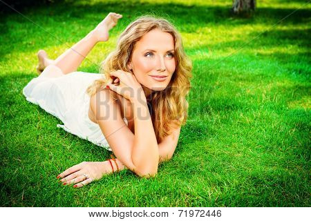 Beautiful smiling woman lying on a grass outdoor. She is absolutely happy.