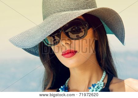 Portrait of a beautiful charming girl posing against the blue sky during summer time