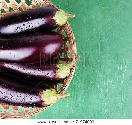 Aubergines in wicker basket on wooden background