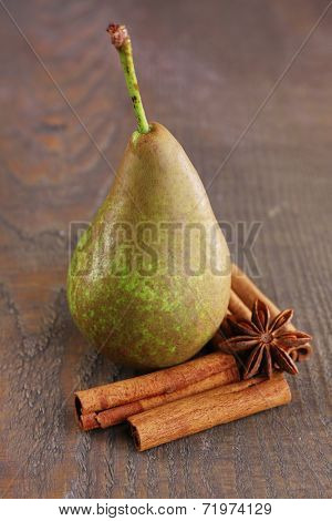 Ripe pear and cinnamon sticks on wooden background