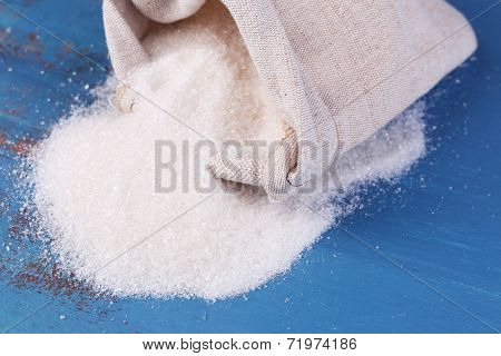 Sugar in bag on color wooden background