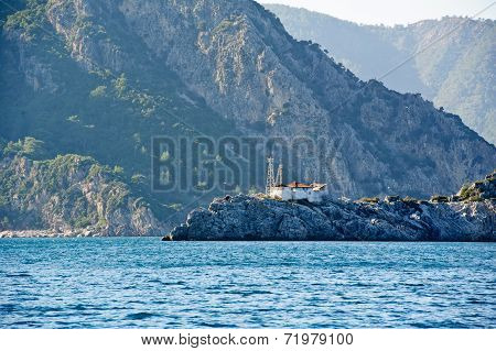 Lighthouse on rocks between haute mountains