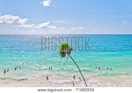 tourists enjoy Caribbean Sea in Tulum, Mexico