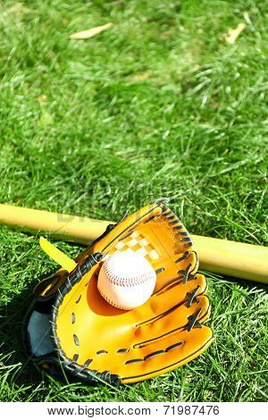 Baseball bat, ball and glove on green grass background