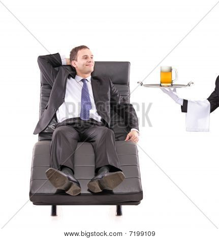Young businessman relaxing on a sofa while the butler serving a beer glass