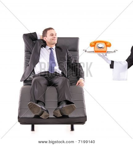 Young businessman relaxing on a sofa while the butler holding a telephone