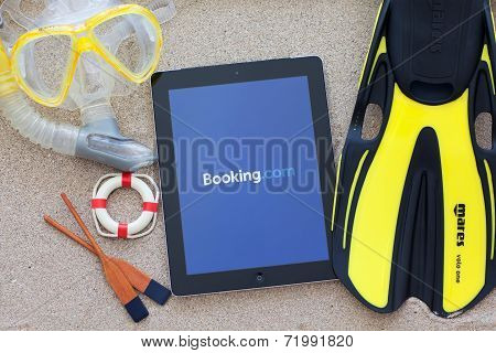 Ipad With App With Booking On The Screen Lying On The Sand With A Set Of Diving