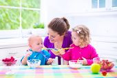 stock photo of child feeding  - Happy young family mother with two children adorable toddler girl and funny baby boy having healthy breakfast eating fruit and dairy sitting in a white sunny kitchen with window - JPG