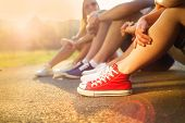 picture of legs feet  - Legs and sneakers of teenage boys and girls sitting on the sidewalk - JPG