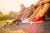 stock photo of adolescent  - Closeup of legs and sneakers of young people on skateboard - JPG