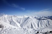 foto of snowy hill  - Winter snowy mountains and blue sky - JPG