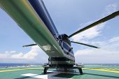 pic of helicopter  - helicopter parking landing on offshore platform. Helicopter transfer crews or passenger to work in offshore oil and gas industry.