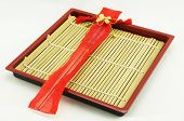 picture of keepsake  - Chopsticks was contained in red container tied with red cord and the exterior has a gold bow attached - JPG